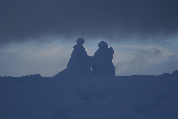 Snow men hold hands atop Arthur's Seat
